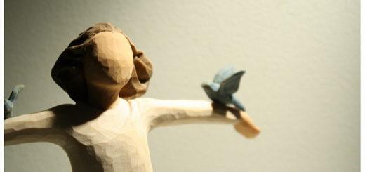 Sculpture en bois d'un personnage recevant deux colombes
