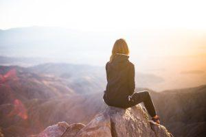 une personne assise au sommet d'une montagne contemple le panorama - Image par StockSnap de Pixabay