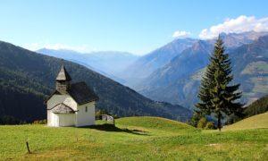 une chapelle dans la montagne, avec un arbre à côté - Image parGreg Montani de Pixabay