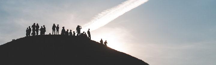 un groupe rassemblé au sommet d'une montagne au lever du jour - Photo by Mariusz Słoński on Unsplash