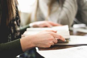 mains d'une femme tenant une Bible au milieu d'un groupe - Photo by Sarah Noltner on Unsplash