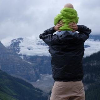 Un père porte son fils sur les épaules devant un paysage de montagnes - Photo by Austin Walker on Unsplash