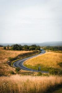 une route sinueuse dans la campagne - Photo by Fabian Grohs on Unsplash