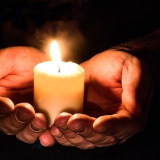 Illustration : deux mains tiennent une bougie allumée dans le noir - Image parMyriam Zilles de Pixabay