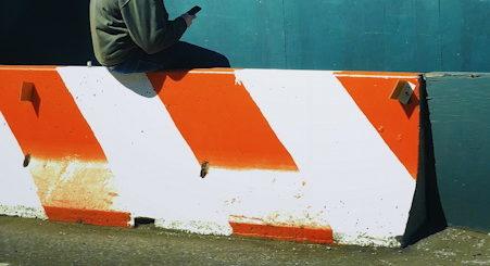 Illustration : homme en sweat à capuche regardant son téléphone - Photo by Jon Tyson on Unsplash
