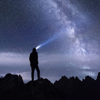 Une personne regarde le ciel étoilé et l'éclaire d'une lampe - photo par stefan stefancik sur unsplash