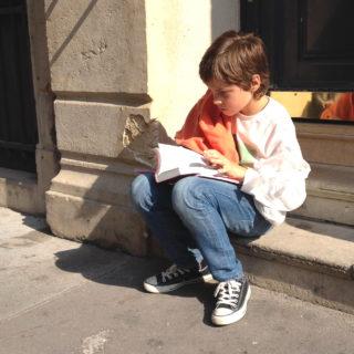 Un enfant, lisant la Bible, assis sur des marches dans la rue - photo par Marc Pernot