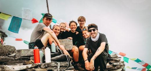 Illustration : groupe de jeunes en randonnée, avec un fond de drapeaux de prière - Photo by Tiago Rosado on Unsplash