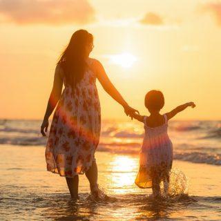 Une mère et sa fillette sur un bord de mer et soleil couchant - Image par Sasin Tipchai de Pixabay
