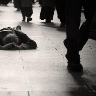 Une personne sur le sol, avec des personnes qui passent à côté - Image parsmokefish de Pixabay