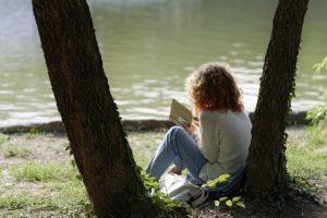 femme lisant dans son psautier devant un lac - Image par Mircea Iancu de Pixabay