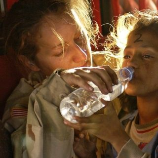 femme aidant une enfant réfugiée à boire - Image par skeeze de Pixabay