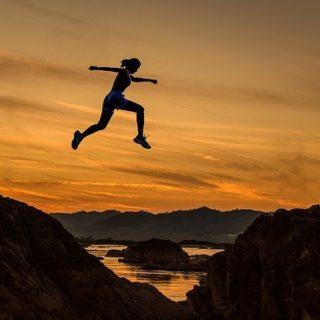 une jeune femme saute par dessus une vallée, sur un fond de coucher de soleil - Image par Sasin Tipchai de Pixabay