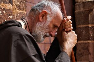 un moine âgé, debout, en prière ou en pensée, appuyé sur un bâton - Image par Qrry de Pixabay