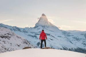 Une personne en doudoune rouge debout sur la neige, face au Cervin - Photo by Joshua Earle on Unsplash